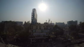 Cityscape view during a train ride through Mumbai, with sun shining on the sky. stock video