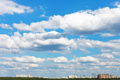 Cityscape with white fluffy clouds in blue sky. Cityscape with white fluffy clouds in spring blue sky Stock Images