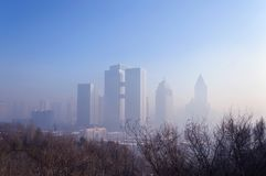 Cityscape of winter Urumqi in smog. View from above of winter Urumqi cityscape in smog with tree branches Stock Photo