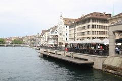 Cityscape of Zurich and river Limmat, Switzerland. Zurich, Switzerland - May 27, 2018 : Exterior view of the buildings.  People relaxing in cafes by the water Stock Photo