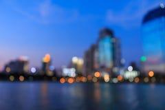 Cityscapeflodsikt på skymningtid, suddigt foto Arkivfoto