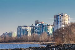 Cityscapes and skyline in clear blue sky on view from river. Sunny autumn day on city beach near river stock image