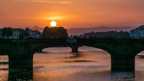 Cityscapesikt på den Arno floden med berömd brotimelapse för helig Treenighet på solnedgången i Florence arkivfilmer