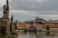 Cityscapesikt på flodstranden med bron och gammal stad i Prague arkivfoto