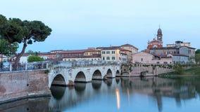 Cityscapesolnedgångtimelapse Rimini Italien panorama Sikt av den Tiberio bron med stadsljus och vatten Dag till natttimelapse arkivfilmer