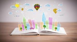 Cityscapeteckning på den öppna boken arkivfoto