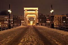 Cityscenic from Amsterdam at night the Netherlands. Thiny Bridge in Amsterdam at night covered with snow in the Netherlands Royalty Free Stock Photos