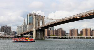 The CitySightseeing Skyline Cruise Ship on the East River beneath the Brooklyn Bridge with Manhattan in the background. Stock Photos