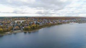 Ciudad agradable de la cabaña de la visión aérea en el banco tranquilo grande del lago metrajes