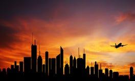 Ciudad céntrica en el amanecer, la silueta del horizonte y el plano Imagen de archivo libre de regalías