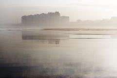 Ciudad costera reflejada en la playa Fotografía de archivo