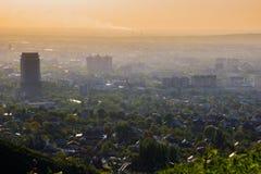 Ciudad de Almaty en la niebla en puesta del sol con niebla con humo y el polvo en el aire, imagen de archivo libre de regalías