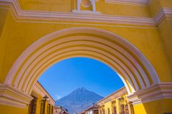 Ciudad de Guatemala, Guatemala, April, 25, 2018: The colorful yellow arch of Antigua city with the active Agua volcano. In the background, Guatemala Stock Photo