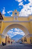 Ciudad de Guatemala, Guatemala, April, 25, 2018: The famous arch of the city center of Antigua together with agua. Volcano in the horizont, view through the Royalty Free Stock Photo