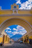 Ciudad de Guatemala, Guatemala, April, 25, 2018: The famous arch of the city center of Antigua together with agua. Volcano in the horizont, view through the Royalty Free Stock Images