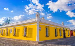 Ciudad de Guatemala, Guatemala, April, 25, 2018: Outdoor view of corner perspective of a bright yellow colonial house. With barred windows in Antigua city in Royalty Free Stock Images