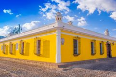 Ciudad de Guatemala, Guatemala, April, 25, 2018: Outdoor view of corner perspective of a bright yellow colonial house. With barred windows in Antigua city in Royalty Free Stock Photography