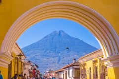 Ciudad de Guatemala, Guatemala, April, 25, 2018: Unidentified people walking in the streets of antigua city and view of. Active Agua volcano in the background Royalty Free Stock Photos
