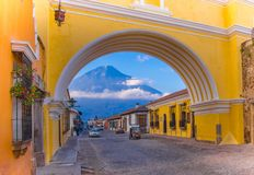Ciudad de Guatemala, Guatemala, April, 25, 2018: View of the active Agua volcano in the background through a colorful. Yellow arch of Antigua city in Guatemala Stock Image