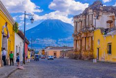 Ciudad de Guatemala, Guatemala, April, 25, 2018: View of antigua city, with some cars waiting over a toned pavement. Street, surrounding of old buildings, and Royalty Free Stock Photo