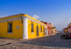 Ciudad de Guatemala, Guatemala, April, 25, 2018: Outdoor view of corner perspective of a bright yellow colonial house. With barred windows in Antigua city in Royalty Free Stock Photos