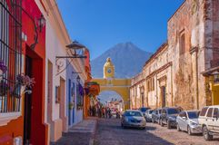Ciudad de Guatemala, Guatemala, April, 25, 2018: Unidentified tourists under a yellow arch waiting for bus in Antigua. City with the active Agua volcano in the Royalty Free Stock Photography