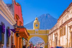 Ciudad de Guatemala, Guatemala, April, 25, 2018: Unidentified tourists under a yellow arch waiting for bus in Antigua. City with the active Agua volcano in the Stock Image