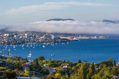 Ciudad de Hobart y río derwent vistos de suburbio de la bahía arenosa con el balanceo de la niebla del mar sobre orilla del este fotos de archivo