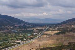 Ciudad de la montaña con el camino y el lago Imagen de archivo libre de regalías