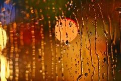 Ciudad de la noche de las fotos hecha a través del vidrio calle Lluvia Imagen de archivo