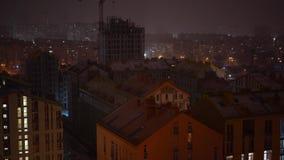 Ciudad de la noche durante nevadas Luces en las ventanas de edificios altos almacen de metraje de vídeo