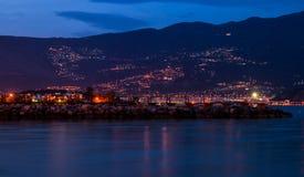 Ciudad de la noche por el mar en el pie de la montaña Foto de archivo