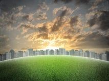 Ciudad de la tarde Edificios y campo de hierba verde Fotografía de archivo