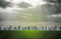 Ciudad de la tarde Edificios y campo de hierba verde Imágenes de archivo libres de regalías