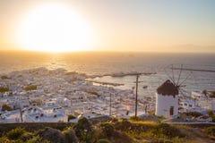 Ciudad de Mykonos con el molino de viento en la puesta del sol, Grecia Imagen de archivo libre de regalías