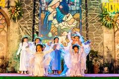 CIUDAD de NAMDINH, VIETNAM - 24 de diciembre de 2014 - creyentes cristianos que cantan un villancico de la Navidad el Nochebuena Imagen de archivo