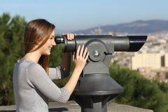 Ciudad de observación de la mujer turística a través de un telescopio Imágenes de archivo libres de regalías