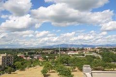 Ciudad debajo del cielo nublado azul Fotos de archivo libres de regalías