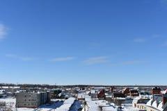 Ciudad del invierno en la nieve en fondo del cielo azul Imagen de archivo