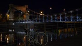 Ciudad del puente en la noche con los coches que caminan gente y las bicicletas almacen de metraje de vídeo