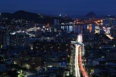 Ciudad del puerto en la oscuridad Las luces de la ciudad reflejan en el agua fotos de archivo