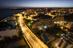 Ciudad en el banco del océano durante puesta del sol Fotos de archivo libres de regalías