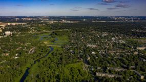 Ciudad en el bosque cerca del río con las nubes de cúmulo fotos de archivo libres de regalías
