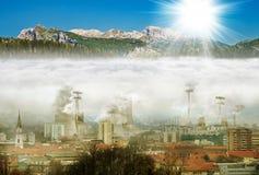 Ciudad en la niebla con humo, montañas con el sol imágenes de archivo libres de regalías