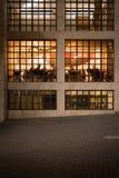 Ciudad en la noche - comensales en café del restaurante a través de la ventana Imágenes de archivo libres de regalías