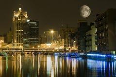 Ciudad en la noche con la luna grande Fotos de archivo libres de regalías