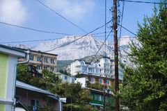 Ciudad en un fondo de una montaña y un polo con los alambres Fotos de archivo libres de regalías