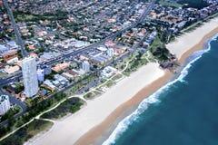 Ciudad enorme delante de una costa Foto de archivo libre de regalías