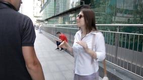 Ciudad grande con los rascacielos Visi?n trasera dos turistas caminan alrededor de la ciudad con una cámara y una charla linda almacen de video