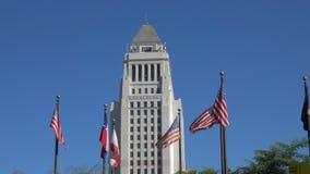 Ciudad Hall Building de Los Angeles y banderas en primero plano durante el día almacen de metraje de vídeo